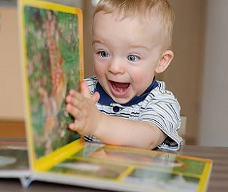 a happy child reading a picture book